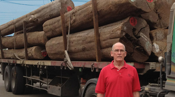 Gib McIlvain standing in front of Teak log truck